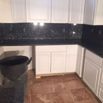 Black Stone Counter With White Cabinets